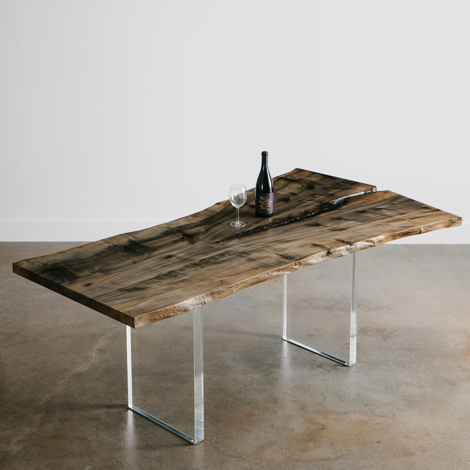 Handmade live edge ebonized dining table with clear lucite base