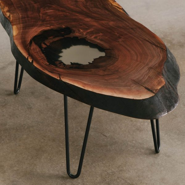 Walnut slab coffee table with clear resin and skinny black steel legs for city apartment