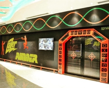 Lazer Runner is located in a 2,000 square foot facility on the first level of Panorama Mall. It's based on a battle zone featuring combat-style tire walls, black lighting, blaring music and artificial fog aimed at confusing your vision and making the objective of tagging opponents a challenge. Lazer Runner is a pure adrenaline rush and up to 12 combatants in glowing vests with laser guns can play simultaneously.