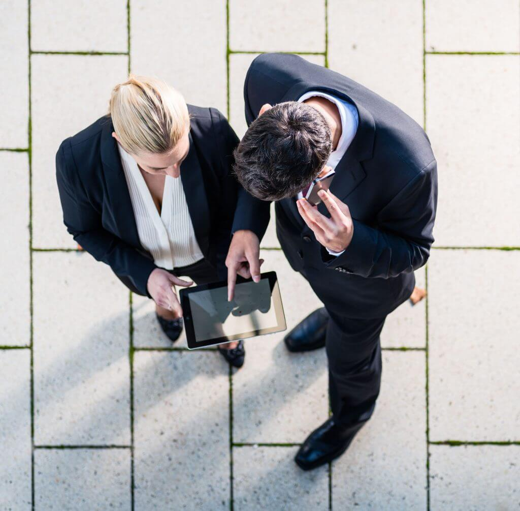 37779211 - business man and woman  with tablet computer standing on square, seen in top view