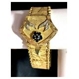 "14k MCM Bracelet Watch, edged by French Rope, Geneva Watch Lid Mounted by Gems; 7"", 49.4g; $950"