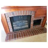 Faux electric fireplace with brick hearth.