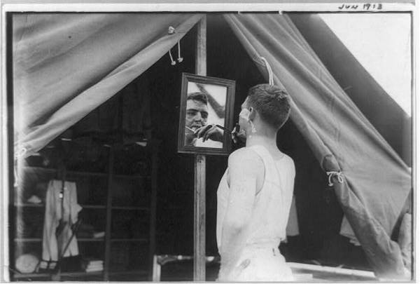 West Point: Cadet shaving in front of tent, June 1913