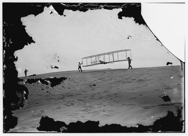 Start of a glide; Wilbur in motion at left holding one end of glider (rebuilt with single vertical rudder), Orville lying prone in machine, and Dan Tate at right; Kitty Hawk, North Carolina