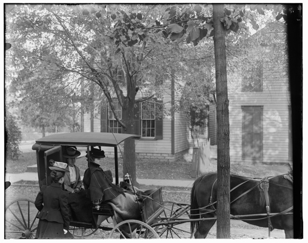 Katharine Wright, Harriet Silliman, and Agnes Osborne in horse-drawn carriage across from Wright home, 7 Hawthorn Street, Dayton, Ohio