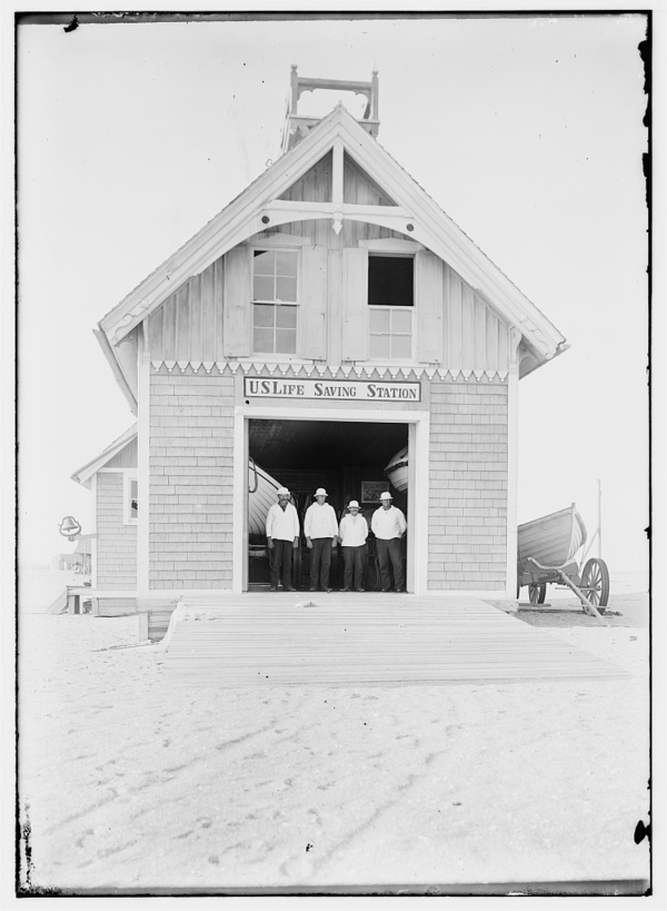 Kill Devil Hills Lifesaving Station, with four crew members wearing white hats and jackets standing in doorway, and a boat near outer wall at right; Kitty Hawk, North Carolina