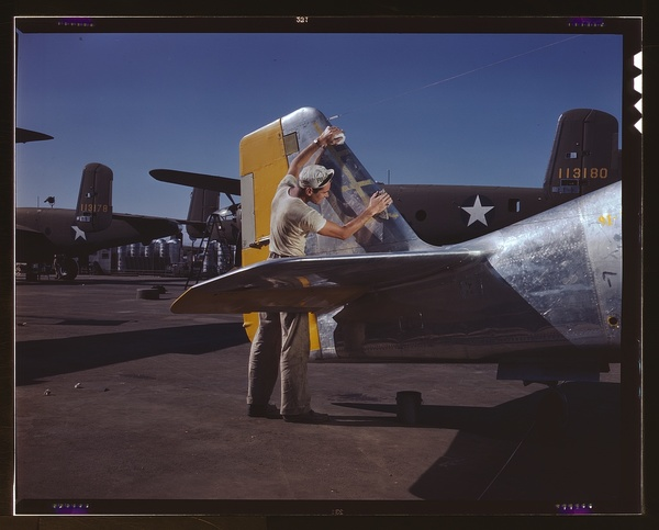 On North American's outdoor assembly line, a painter cleans the tail section of a P-51 fighter prior to spraying the olive-drab camouflage of the U.S. Army, North American Aviation, Inc., Inglewood, Calif.