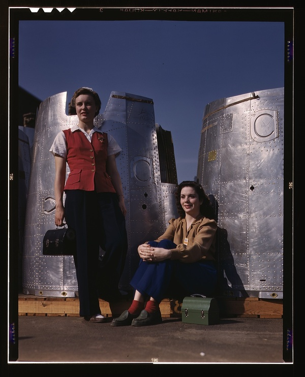 Two assembly line workers at the Long Beach, Calif., plant of Douglas Aircraft Company enjoy a well-earned lunch period, Long Beach, Calif. Nacelle parts of a heavy bomber form the background