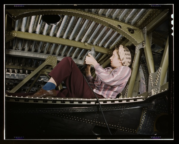 An A-20 bomber being riveted by a woman worker at the Douglas Aircraft Company plant at Long Beach, Calif.