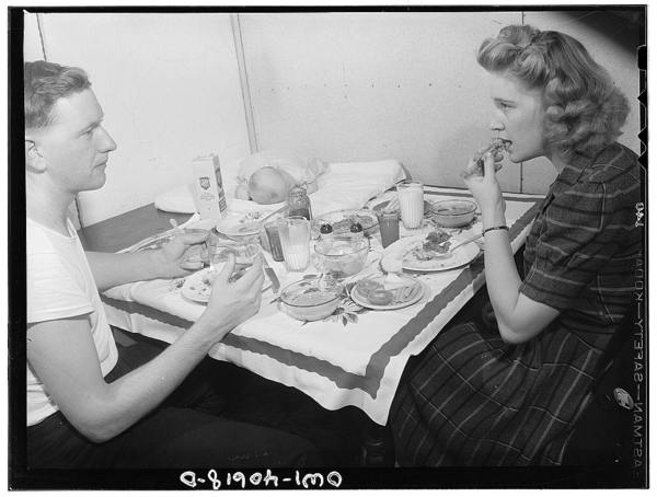 Washington, D.C. Hugh Massman,  a second class petty officer who is studying in Washington, and his wife eating dinner. Joey, their son, sleeps on a pad on the table