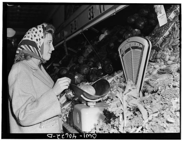 Washington, D.C. Lynn Massman, wife of a second class petty officer who is studying in Washington, shopping for groceries. While Lynn shops, her landlady keeps an eye on baby Joey