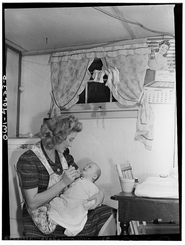 Washington, D.C. Lynn Massman, wife of a second class petty officer who is studying in Washington, D.C., feeding an eight weeks old son cereal