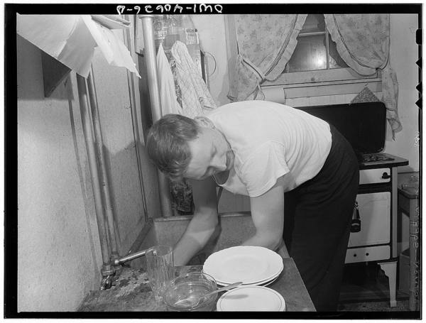 Washington, D.C. After dinner, Hugh Massman, a second class petty officer who is studying in Washington, does the dishes while Lynn feeds the baby