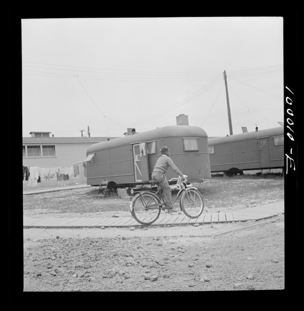 Arlington, Virginia. FSA (Farm Security Administration) trailer camp project Young occupant gets around by bicycle. The community building is in the background