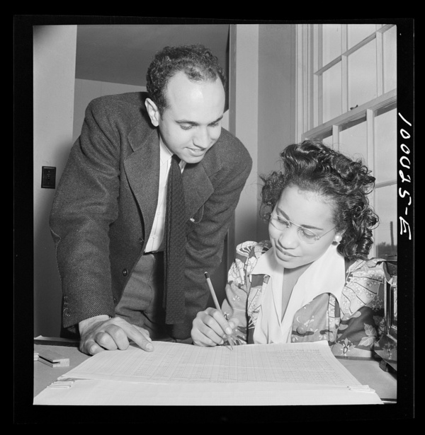 Arlington, Virginia. FSA (Farm Security Administration) trailer camp project Manager of the project going over rental plan with his secretary