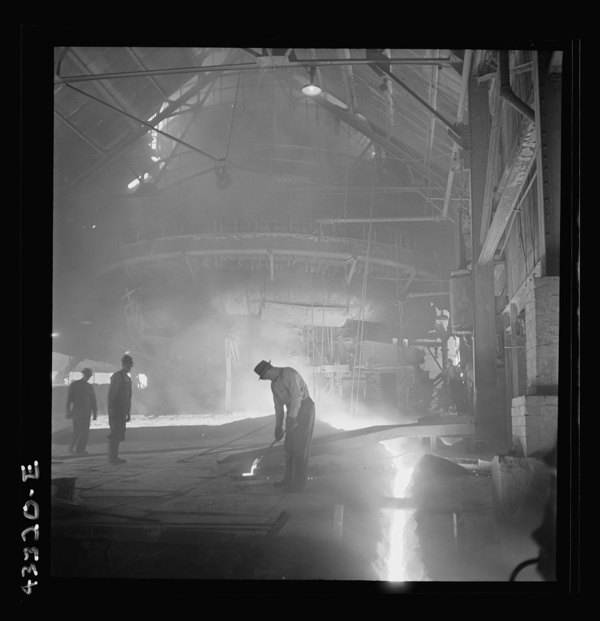 Columbia Steel Company at Ironton, Utah. Tapping a heat of iron in the cast house of the blast furnace