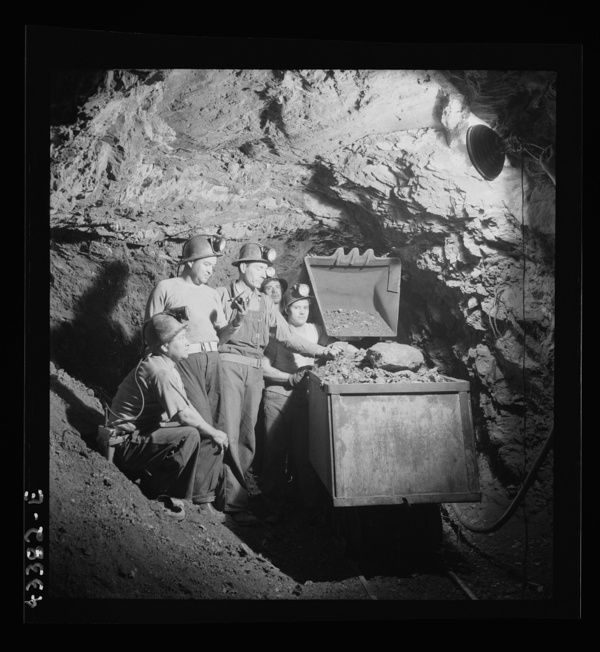 New Idria, California. Loading cinnabar, an ore containing mercury and sulphur, into a mine car with a mechanical loader. Triple-distilled mercury is produced from the ore at the New Idria Quicksilver Mining Company