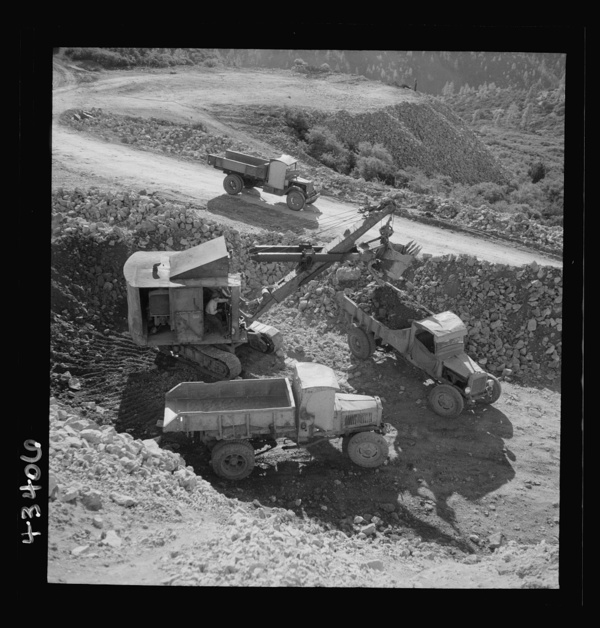 New Idria, California. Trucks, shovel, and crane used in loading cinnabar, an ore containing mercury, at an open-cut mine of the New Idria Quicksilver Mining Company's workings
