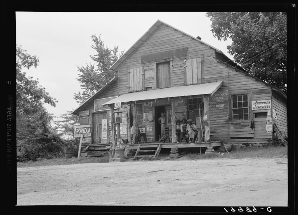 Country store on dirt road, Sunday afternoon. Note kerosene pump on right and gasoline pump on the left. The brother of the owner of the store stands in the doorway. Near Gordenton, North Carolina