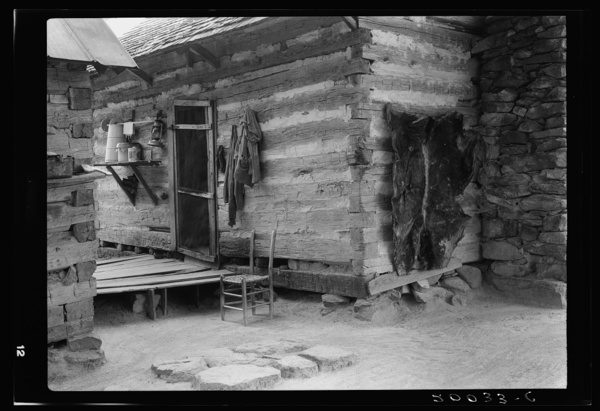 Construction detail of double log cabin of share tenants. The cowhide was hung there after being dried on a barn to be used as floor covering. Shelf shows churn, also bucket of water in which baby's bottle is kept cool. Person County, North Carolina