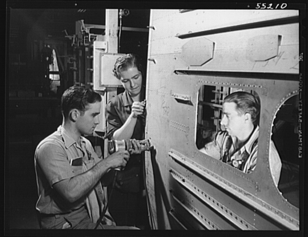 Kansas City, Kansas. A young woman and two men, employees of North American Aviation, Inc., riveting the skin assembly of a plane