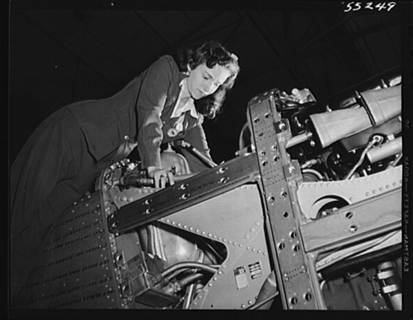 A woman employee on the P-51 Mustang fighter assembly line at North American Aviation adjusts the engine controls before the plane moves down the assembly floor