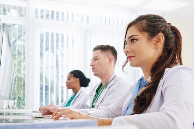 Duas mulheres com jaleco branco e um homem com jaleco branco estão sentados em frente a uma tela de computador.