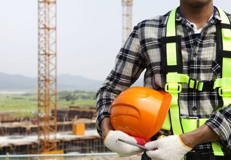 O tronco de um homem que está com um colete de proteção, segurando um capacete com as mãos vestidas de luvas de proteção também. Ao fundo, uma estrutura de indústria.