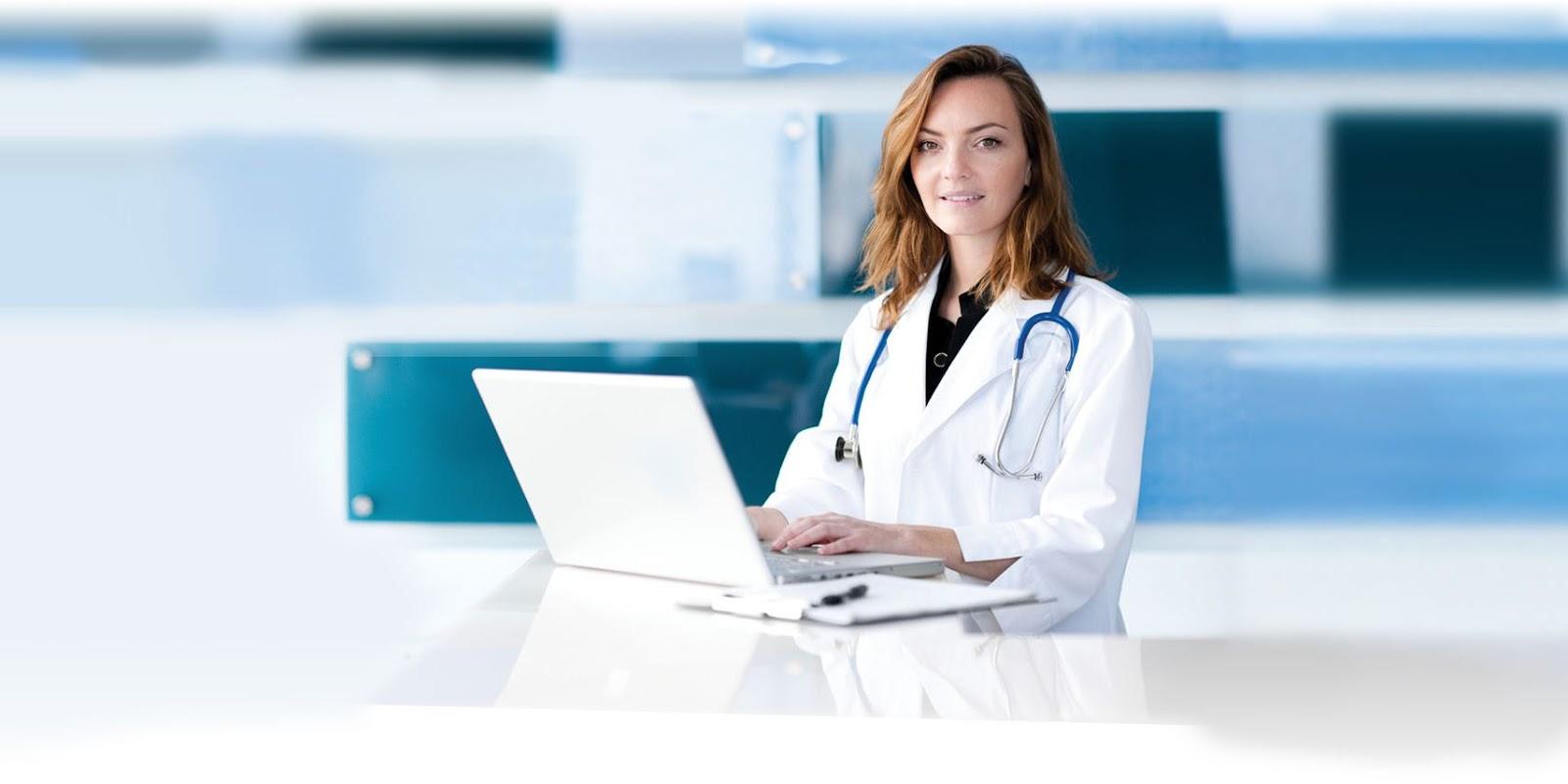 Uma médica com cabelos loiros, usa jaleco e tem um estetoscópio no pescoço. Ela digita em um computador em cima de uma mesa branca com um fundo claro e tons de azul.
