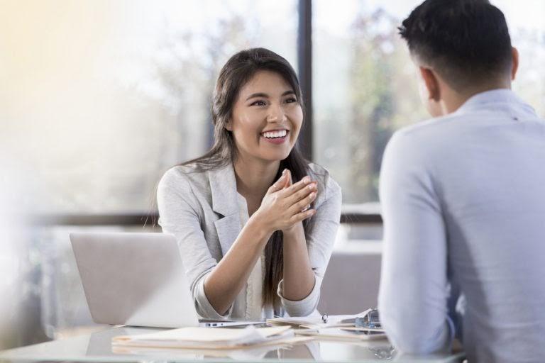 Uma mulher de cor amarela vestida com um jaleco branco conversa com um homem que está de costas para a câmera, na mesa temos um computador e papéis.