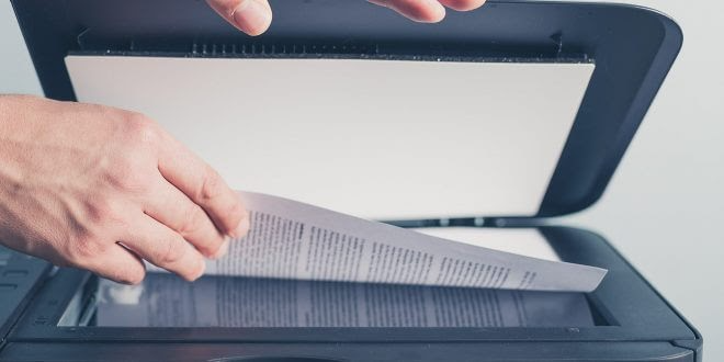 Uma folha que pertence a algum documento está sendo colocada na digitalizadora.