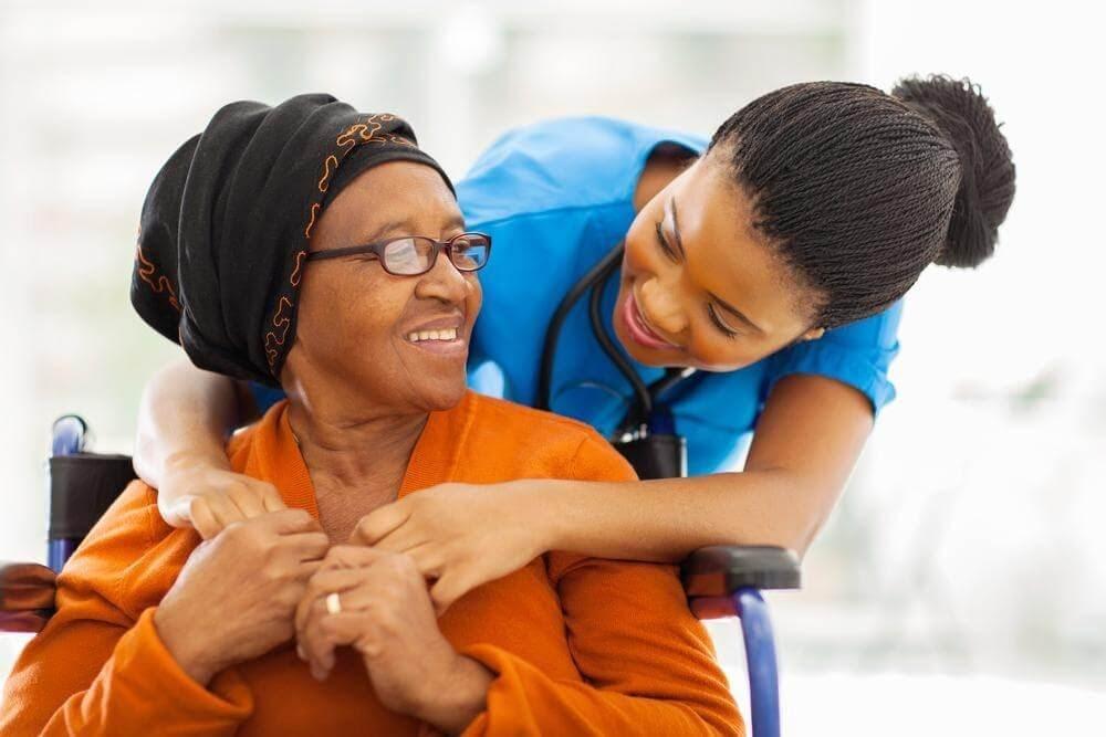 Uma mulher idosa negra está sentada em uma cadeira de rodas sorrindo, recebe um abraço de uma médica negra com jaleco azul e com um medidor de pressão no pescoço.