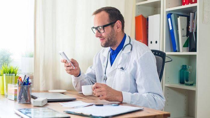 Um médico de pele branca segura uma xícara de café em uma mão e na outra um celular. Em sua mesa tem um computador e papéis.