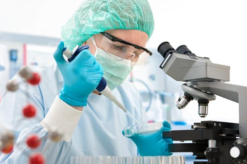 Uma mulher com luvas, jaleco, toucas e óculos de proteção segura um medidor de amostras perto de um microscópio.