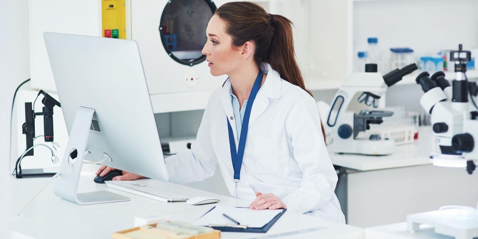 Uma mulher de jaleco branco, está sentada na frente de um computador. Atrás dela, vemos microscópios e equipamentos laboratoriais.
