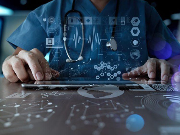 Uma mão de um médico mexe em um tablet em que saem ícones digitais.
