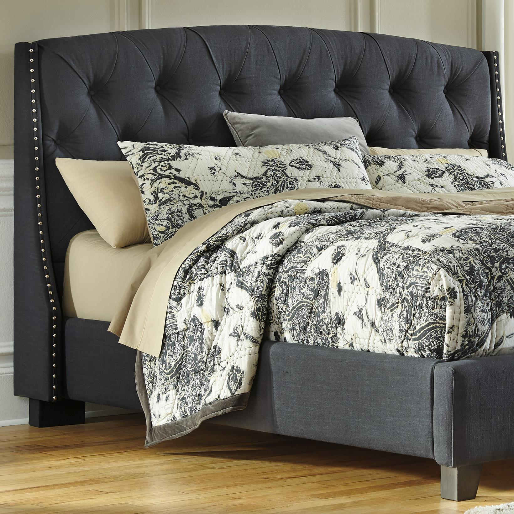 king upholstered headboard in dark gray with tufting and nailhead trim