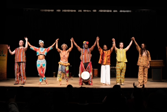 Seven dancers bowing onstage holding hands