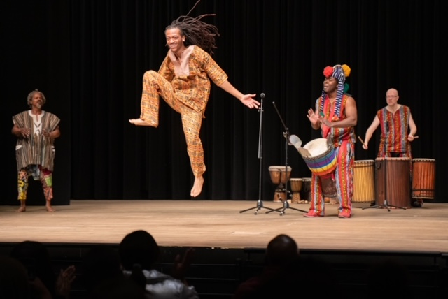 Dancer and drummer onstage, the dancer is airborn