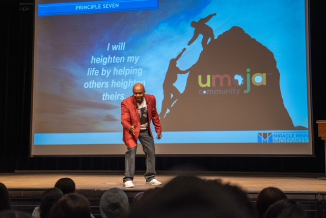 Man onstage in front of Umoja screen