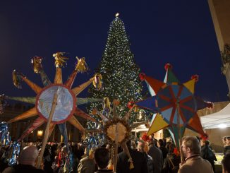 people hold traditional ukrainian decorations during the christmas tree lighting ceremony in st. peter's square.