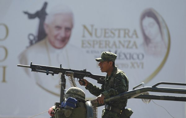 soldiers keep watch near a large poster promoting the visit of pope benedict xvi in leon