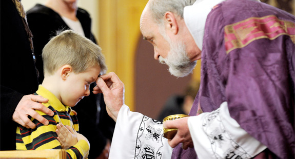 Six-year-old Luke Likoudis receives ashes from Father John Tokaz during a 2011 Ash Wednesday Mass at St. James the Apostle Church in Trumansburg