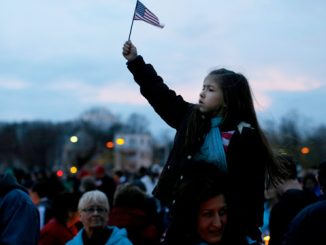 A girl holds up a U.S. flag during a candlelight vigil in the Dorchester section of Boston April 16