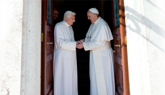 Retired Pope Benedict XVI greets Pope Francis at the Vatican May 2. The 86-year-old retired pontiff