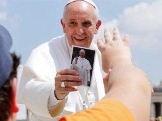 Pope Francis receives a postcard with a photograph of himself as a gift at the end of his weekly audience in St. Peter's Square at the Vatican May 8. (CNS photo)