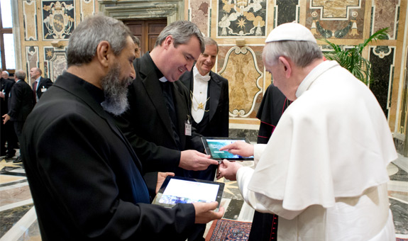 Pope Francis launches the smartphone app Missio during an audience with national directors of pontifical mission societies May 17 at the Vatican. Holding the iPad for the pope is Oblate Father Andrew Small