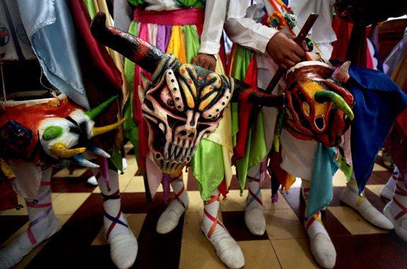 Men hold traditional devil masks during Corpus Christi mass celebrations at the San Atanacio church in La Villa