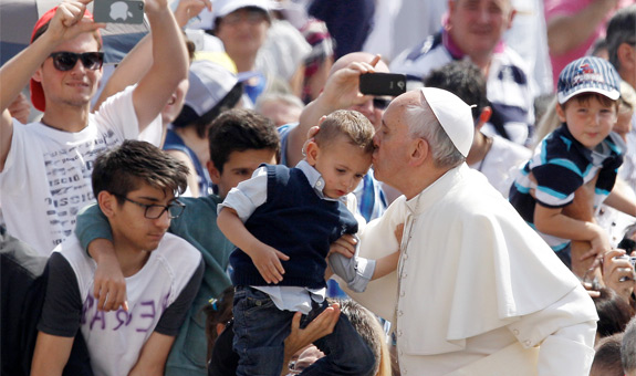 Pope Francis kisses a boy as he arrives for his weekly general audience in St. Peter's Square at the Vatican June 5. (CNS photo/Paul Haring) (June 5