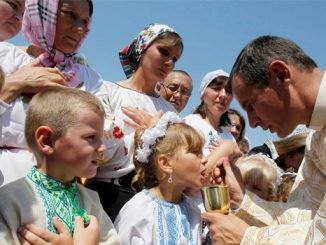A girl receives communion from an Ukrainian Greek Catholic priest during the annual gathering and pilgrimage to the miraculous icon of 'Halytska' (the Mother of God) in the village of Krylos